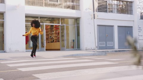 Fashionable young black woman with afro hair running across the street, full length, close up