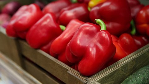 Footage of fresh ripe red sweet bell pepper in box on sale at grocery food store.Close up.Buy natural tasty food ingredients for healthy eating