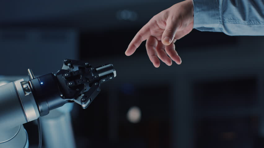 Futuristic Robot Arm Touches Human Hand in Humanity and Artificial Intelligence Unifying Gesture. Conscious Technology Meets Humanity. Concept Inspired by Michelangelo's Creation of Adam | Shutterstock HD Video #1026344132