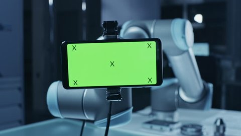 Robot Arm Holding Green Mock-up Screen Smartphone in Landscape Mode, Smoothly Moving into Focus. Industrial Robotic Manipulator End Effector Holds Mobile Phone with Chroma Key Display.