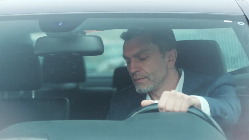 Close up view of handsome man in luxurious car impatiently beeping car horn while not moving in the traffic jam, then angrily talking on the phone and actively waving his arms. Stress, trouble