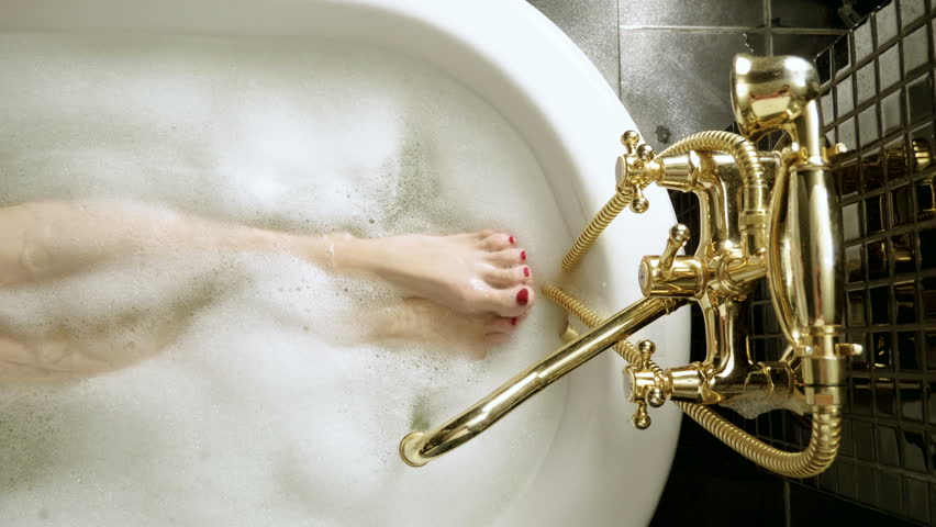 Top view of water flowing from golden faucet into the bathtub. The slim legs and feet with red pedicure of young woman taking a bubble bath. 4K | Shutterstock HD Video #1026371582