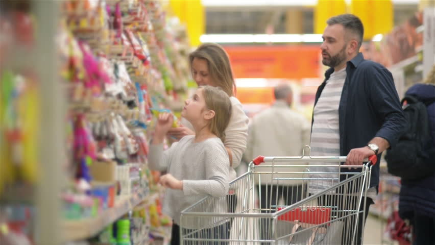 Beautiful Couple And Their Daughter Are Having Fun While Doing Shopping In Supermarket. #1026374762