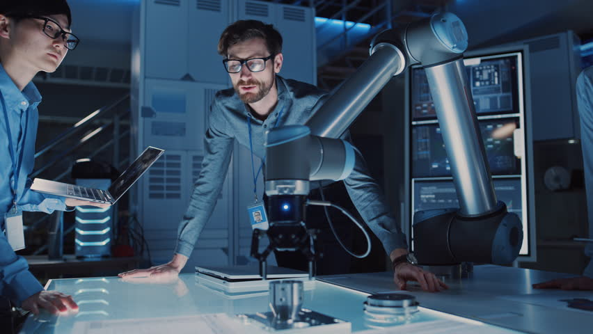Diverse Team of Engineers with Laptop and a Tablet Analyse and Discuss How a Futuristic Robotic Arm Works and Moves a Metal Object. They are in a High Tech Research Laboratory with Modern Equipment. #1026410222