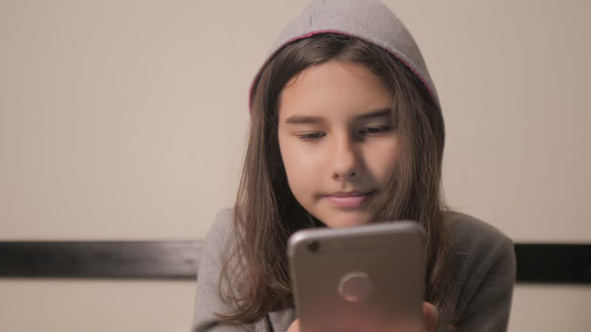 Online shopping online retail service based . little teen girl in the hood writes a message chatting in social media messenger. children technology and communication concept. teenage girl lifestyle | Shutterstock HD Video #1026455282