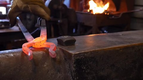 A Blacksmith Forging the Jaws on a Pair of Tongs in the Blacksmith Shop at the Anvil