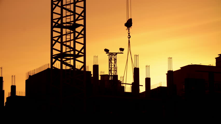 Silhouette of tower crane working on construction site elevate concrete mixer, constructors working on residential building sunny evening, golden hour, warm orange sky