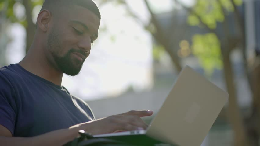 Bottom view of young Afro-American short-cut muscular man with stylish beard in blue T-shirt sitting on bench in park, working on laptop. Sun shining. Lifestyle, work concept