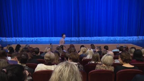 Saratov / Russia - March 29, 2019: People in the auditorium of the theater before the performance or in the intermission. Blue curtain on stage. Shooting from behind.