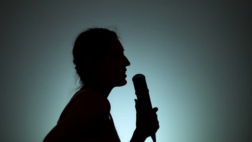 Silhouette of a woman. The shadow of a woman on a light background. The woman is singingin a microphone. Emotions, song. Slow motion. | Shutterstock HD Video #1026658562
