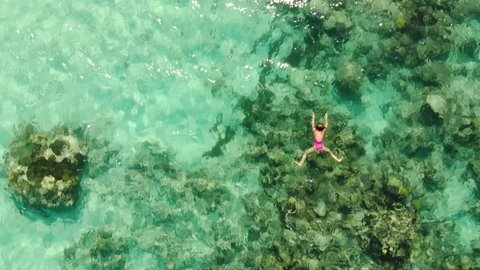 Girl in a pink swim suit snorkeling alone around a reef in the Beautiful blue and crystal clear waters with a coral reef, Aerial footage,