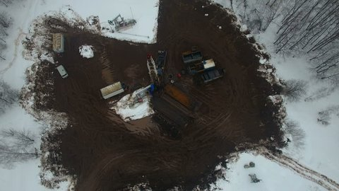 Drilling a deep well with a drilling rig in an oil and gas field in winter forest. The field is located in Kamchatka, Tundra, Yamal, North, West, Siberia, fog, smoke, aerial up view