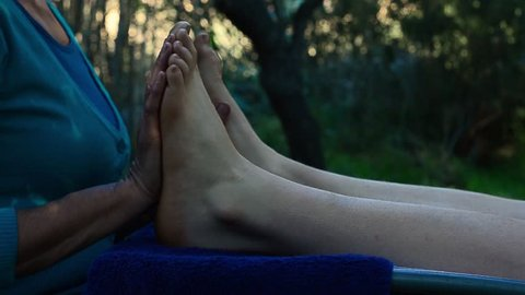 Reflexology foot massage treatment in tranquil zen environment in nature, female massage therapist preforming reflexology on young woman at health spa retreat, lady enjoying a pampering massage