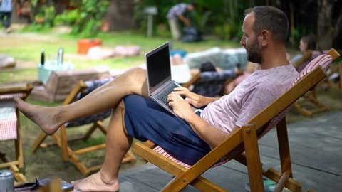 Young man working with laptop on sunbed in the park