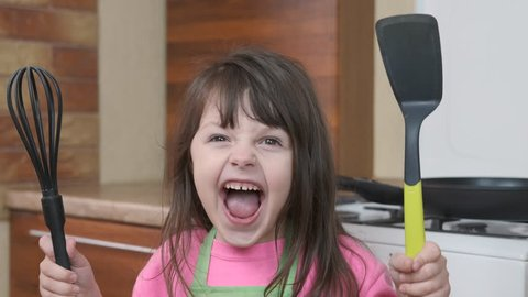 Cheerful child in the kitchen. Funny little girl with corolla and trowel.