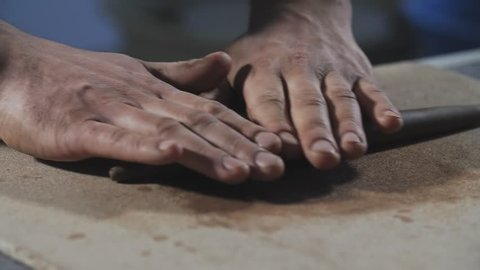 Potter rolls clay. Man hands making clay product in slow motion. Potter's work close-up.