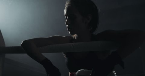 Tired female boxer rests on the ropes of the ring. Silhouette. Boxing concept