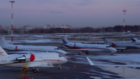 Panoramic view of a large number of aircraft parked at the airport. Business jets and large passenger liners, medium-sized planes. Evening. Sunset, orange and purple clouds in the background. 4K