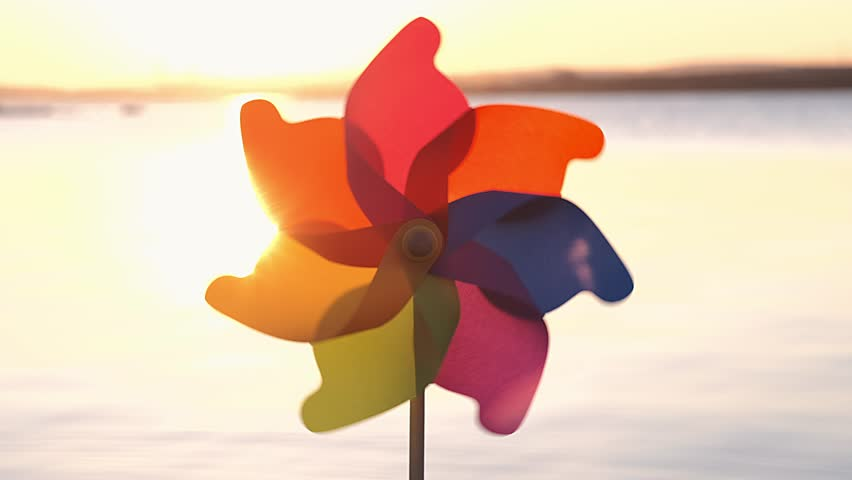 A rotate colored plastic pinwheel with a blowing wind stands on sand by the sea against the smooth surface of the sea and a bright pink sunset. Toy mill on the beach. Large disk of the sun. Copyspace | Shutterstock HD Video #1026838832
