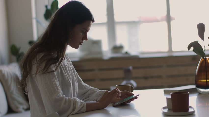 Elegant girl holding smartphone sitting indoors cafe backlit 4k side view. Portrait of young woman typing mobile phone at coffee break natural light cozy interior. Modern technologies social networks  | Shutterstock HD Video #1026861752