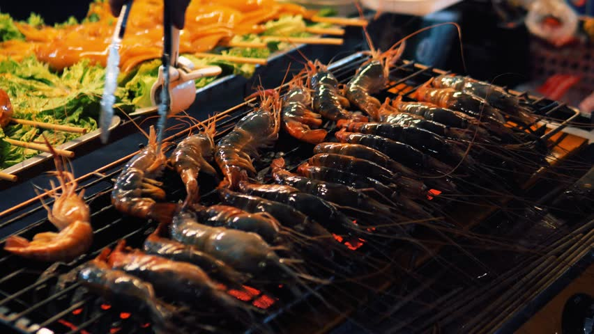 Grilling shrimps on barbecue. Hand puts the shrimp on grill. Grilled seafood on bbq. grilled shrimps at street food festival. Cooking seafood on grill at Bangkok , Thailand