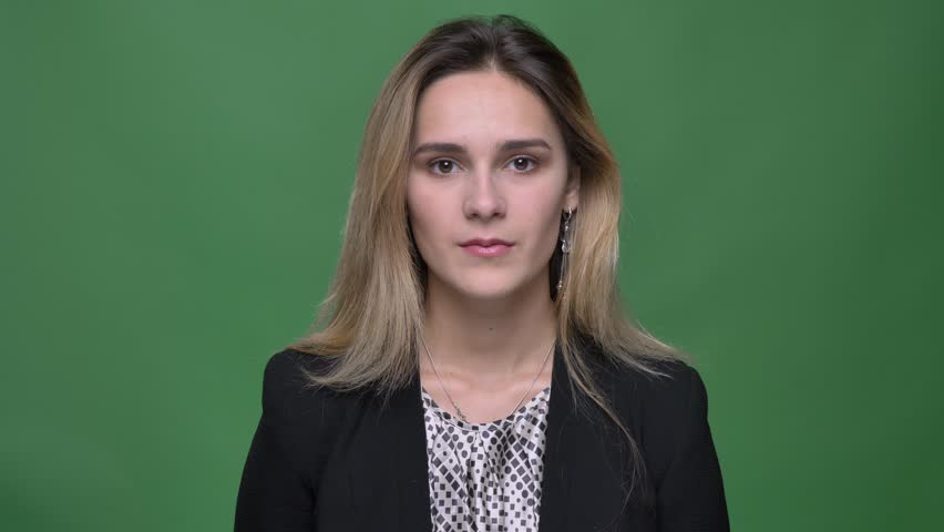Closeup shoot of young attractive hipster caucasian female looking straight at camera with background isolated on green | Shutterstock HD Video #1026885302