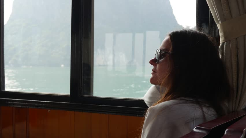 A young woman sitting inside a boat in a white sweater and sunglasses is looking at the beautiful view of the bay. Travel concept | Shutterstock HD Video #1026897722