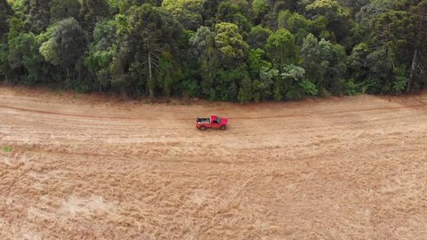 Solo pickup truck cruising on the empty agricultural fields of Brazil at the time of seeding season (drone shot)
