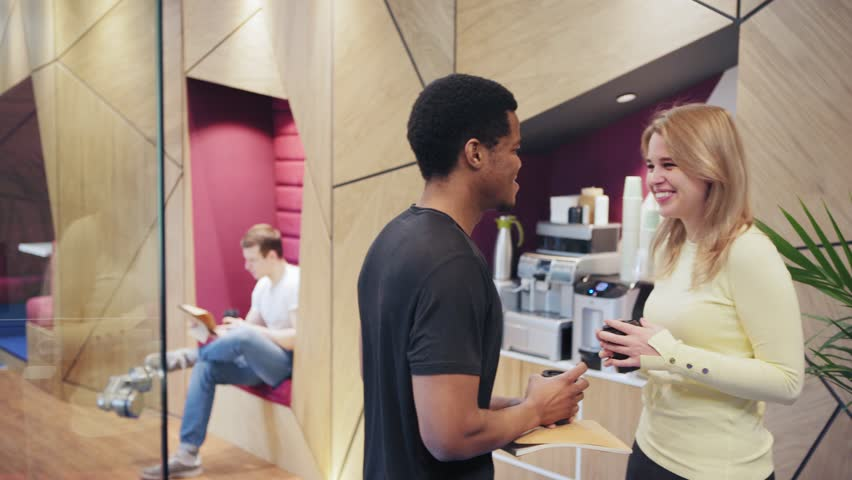 Two young professionals, African man and Caucasian woman, standing near espresso machine at office, drinking coffee and talking friendly at break | Shutterstock HD Video #1026938102