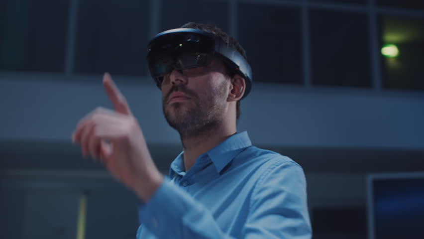 In 3D Content Creating Laboratory Engineer Wearing Professional Virtual Reality Headset Works and Gestures in Augmented Reality. Stylish Low Angle Arc Portrait Shot | Shutterstock HD Video #1026992702