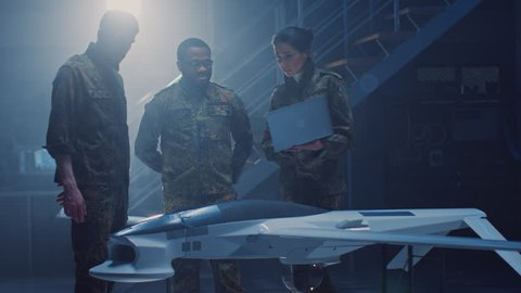 Army Aerospace Engineers Work On Unmanned Aerial Vehicle / Drone. Uniformed Aviation Experts Talk, Using Laptop. Industrial Facility with Aircraft for: Surveillance, Warfare Tactics, Air Strike
