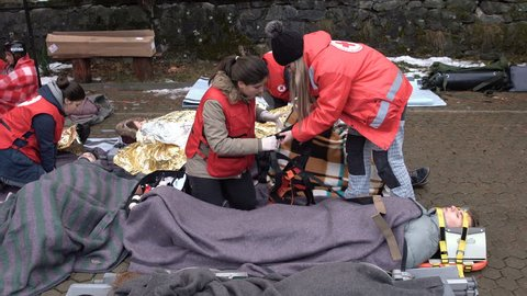 Sofia, Bulgaria - 5 December 2018: Volunteer paramedics from Bulgarian Red Cross Youth provide first aid with a stretcher during a training for saving people in an accident.