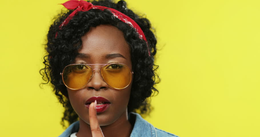 Close up of the young cheerful African American woman in glasses and stylish outfit smiling to the camera and doing gesture hush, be silent with finger to the lips on the yellow background. Portrait. | Shutterstock HD Video #1027041542