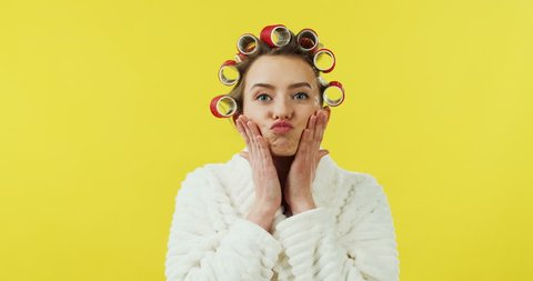 Portrait of the young Caucasian pretty woman in the white bathrobe and curlers having fun and making funny faces to the camera on the yellow background.