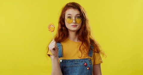 Portrait of the young pretty caucasian red-haired girl in sunglasses looking fuuny at the camera and eating big colorful lollipop on the yellow wall background.