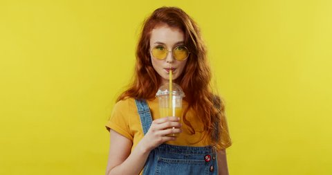 Portrait of the charming red-haired girl in sunglasses drinking orange juice and smiling to the camera on the yellow wall background.