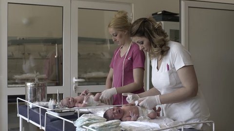 Midwives changing diapers newborn babies on table at maternity ward.
