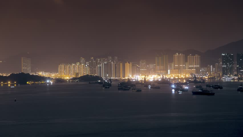 Time lapse. View of busy and foggy bay between Kowloon and Hong Kong Island full of boats, ferry, ships. Illuminations on buildings.