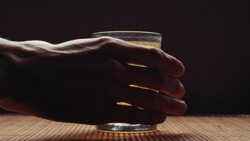 A man's hand picks up a glass of fizzy water from a table on a black background | Shutterstock HD Video #1027090892