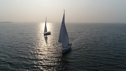 Aerial view of two sloops at sundown are sailing boats with single mast and fore-and-aft rig plus one head-sail the most common setup of modern sailboats is the Bermuda-rigged configuration 4k quality