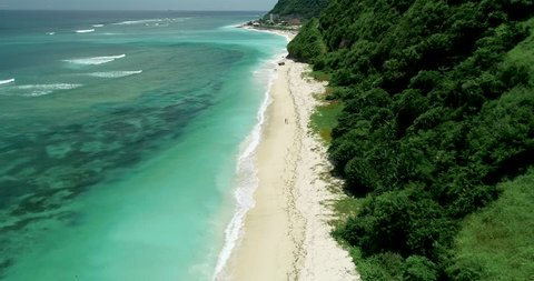 Stunning Aerial shot of young romantic couple walking on a secluded white sand beach with crystal clear blue ocean and waves in Pandawa, Bali – 4k Drone Footage