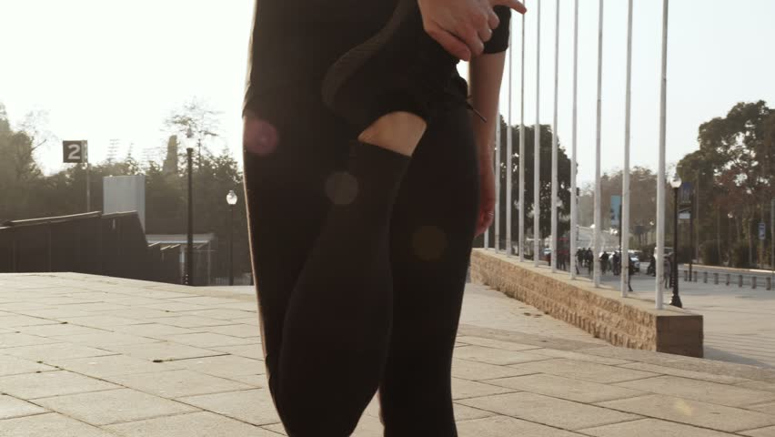 Woman in a black tracksuit stretches leg muscles before Jogging down the street in Sunny warm weather. Young girl doing useful exercises for health. Woman bends his leg backwards to pump the muscles #1027180862