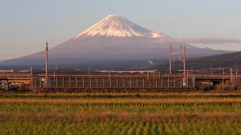 Mount Fuji, Shizuoka, Honshu, Japan - CIRCA 2017: Shinkansen Bullet Train passing through harvested rice fields below the snow capped volcano