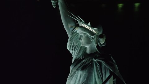 Aerial view of the Statue of Liberty with the view of lower Manhattan in the background, New York City, at night during winter. Shot on 4k RED camera.