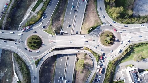 Highway interchange junction with traffic aerial top down view footage from drone with vehicles driving on freeway, roundabout and ramp lanes, 4K video of transportation from above