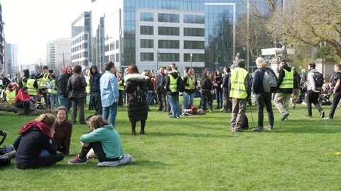 Brussels, Belgium - March 30, 2019:Original view of yellow vest protesters and entertaining young people walking and discussing something on a green lawn in Belgium in spring
