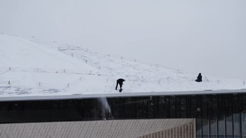 A man in a helmet with a shovel throws snow from the roof of a building, snow falling from the roof. Handheld shot of man cleaning snow from the roof of big building, two workers having a rest