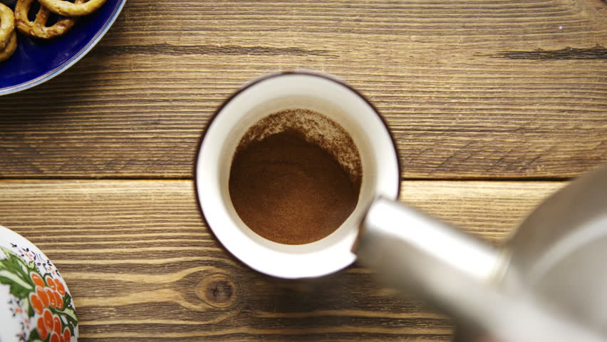 Top view of hot water slow poured into white cup with instant coffee.   Shutterstock HD Video #1027334222