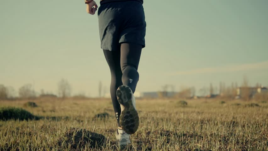 Man Running Slow Motion On Field.Close Up Foot And Running Shoes.Runner Legs Close-Up Jogging In Slow Motion.Male Endurance Workout For Marathon Race.Man Fit Athlete Legs Jog.Sport ,Recreation Concept #1027360622