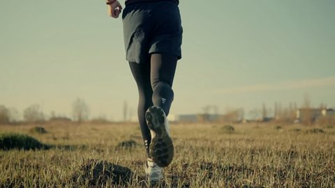 Man Running Slow Motion On Field.Close Up Foot And Running Shoes.Runner Legs Close-Up Jogging In Slow Motion.Male Workout Outdoor At Spring Sun.Man Athlete Legs Jogging Rear Back View From Gimbal.